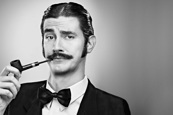 Mono image of a man with a pipe and bow tie
