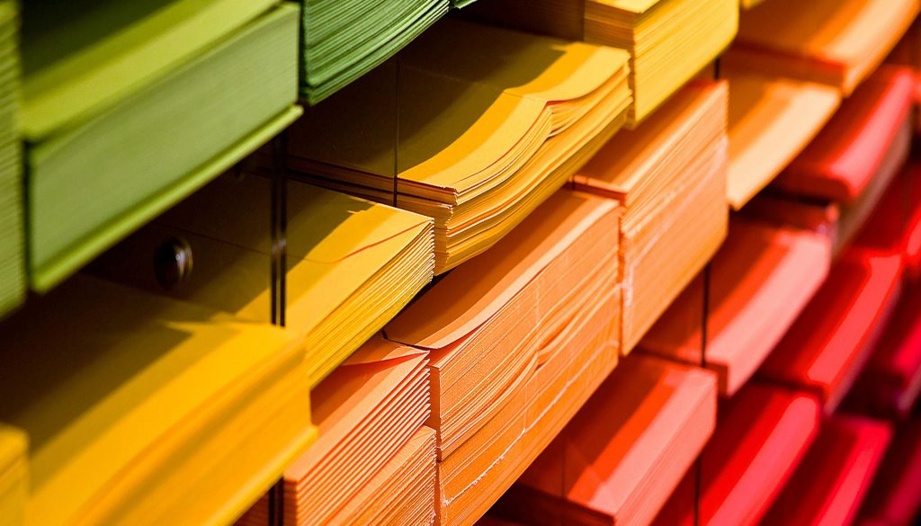 Stacks of coloured paper in a pigeon hole